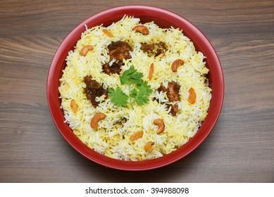 Top view of delicious North Indian food Hydrabadi chicken biriyani, Dum Biriyani, Chicken pulao seasoned corriander leaves. basmati rice, herbs, raitha.  Ramadan Kareem, Eid-Ul-Adha
