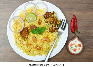 Top view of delicious North Indian food Hydrabadi chicken biryani, Dum Biriyani, Chicken pulao seasoned with mint leaves, basmati rice, herbs, raitha for Ramadan Kareem, Eid-Ul-Adha, Diwali