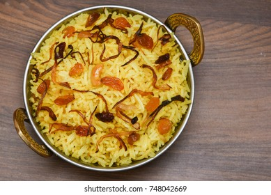 Top view of delicious North Indian food vegetable pulao or biryani in copper or brass vessel. Made of  basmati rice, curd  and pickle side dish.