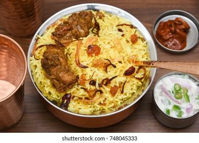 Top view of delicious North Indian food Hydrabadi chicken biryani, Dum Biriyani, Chicken pulao made with basmati rice, spices. Yogurt, pickle side dish  for Ramadan, Eid festival.