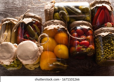 top view of delicious pickles in jars on wooden table