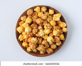 Top view of delicious popcorn in round wooden plate isolated on white background. Include buttery caramel corn and rich cheddar cheese corn. Food and snack concept.