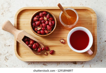 Top view of delicious rose hip tea in cup with dried rose hips on wooden tray.