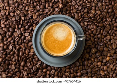 A top view of a delicious transparent glass cup of hot cappuccino standing on and surrounded by coffee beans