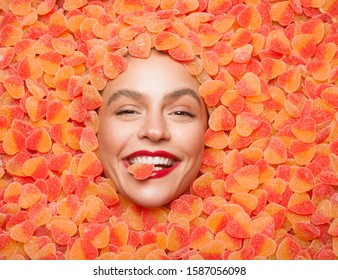 Top view of delighted young female with bright makeup smiling and biting jelly candy while lying in pile of heart shaped sweets