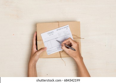 "Top view of deliveryman making notes in ""return to vendor"" delivery receipt at table"