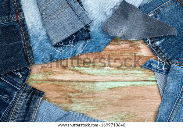 Top view of denim scraps from old jeans. On a painted hardwood floor. Room for copy.