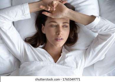 Top view of depressed sad young woman lie relax in bed look in distance thinking remembering, upset stressed millennial female rest in home bedroom feel sick suffer from illness or depression