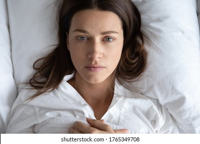 Top view of depressed upset young woman lie relax on white pillow linen sheets feel distressed lonely, sad millennial female rest in home bedroom suffer from depression or insomnia, having problems