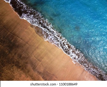 Top view of a deserted beach. Coast of the island of Tenerife, Canary Islands, Spain. Aerial drone footage of sea waves reaching shore.