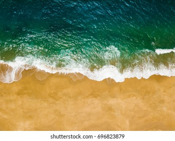 Top view of a deserted beach. The Portuguese coast of the Atlantic Ocean. Aerial drone photo of ocean waves reaching shore.