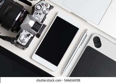 Top view of designer, blogger or photographer working table. Graphic tablet, tablet pc, laptop, smartphone and photo camera laying on white table.