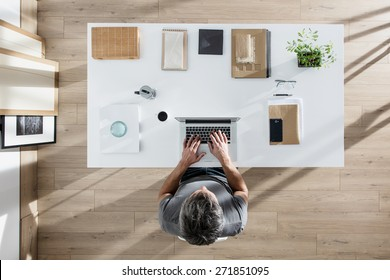top view, designer sitting at desk and working on his laptop, his table is perfectly tidy, the sun casts graphics shadows on the wood floor