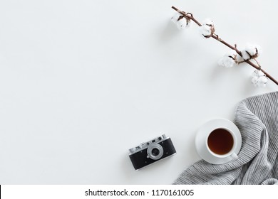 Top view of desk fo photographer with vintage camera, tea, warm blanket on white background. Flat lay with copy space.