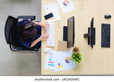 top view of the desk in the office of an Asian woman who is sitting in front of the computer and sheet of statistics and graphs information. By sitting alone Which the opposite table has no people com