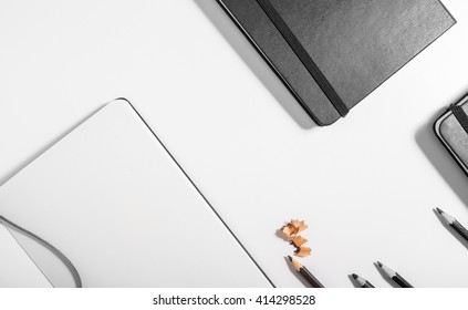Top view of a desktop consisting on Black pencils, a notebook, on a withe desk background