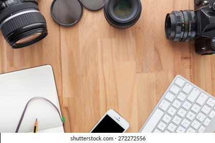 Top view of a desktop of a photographer consisting on a cameras, a keyboard, a smart phone  on a wooden desk background