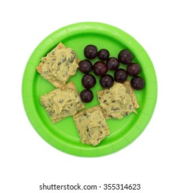 Top view of a diet meal of several spinach hommus on whole grain crackers with grapes upon a green paper plate isolated on a white background.
