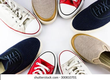 Top view of different colorful men's shoes in the circle isolated on white background