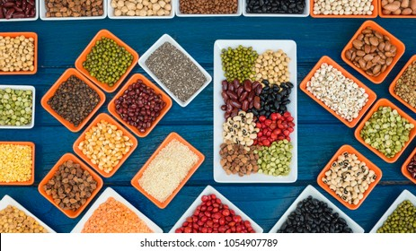 Top view different dry legumes in container on blue plank, Multicolor dried beans for eating healthy