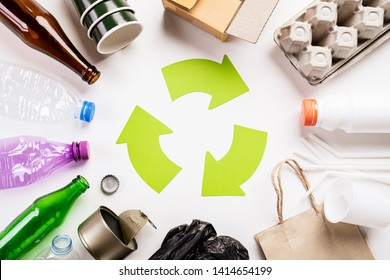 Top view of Different garbage materials with recycling symbol on white wooden table background. Recycle, World Environment Day and Eco concept