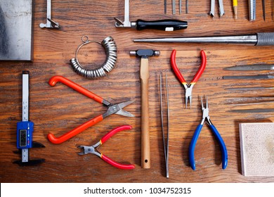 Top view of different goldsmiths tools on the jewelry workplace. Desktop for craft jewelry making with professional tools. Set of tools over rustic wooden background.