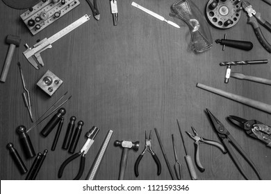 Top view of different goldsmiths tools on the jewelry workplace. Desktop for craft jewelry making with professional tools. Aerial view of tools over rustic wooden background. Postcard design
