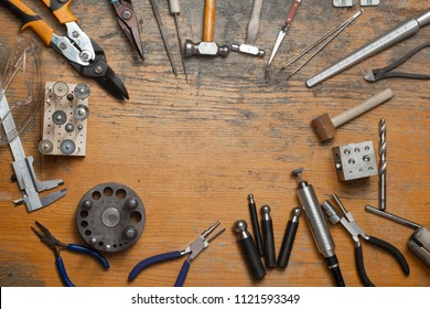 Top view of different goldsmiths tools on the jewelry workplace. Desktop for craft jewelry making with professional tools. Aerial view of tools over rustic wooden background. Poster design.