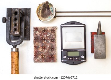 Top view of different goldsmiths tools on the jewelry workplace. Desktop for craft jewelry making with professional tools. Aerial view of tools over isolated white background. Tabl repair goldsmith