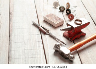 Top view of different goldsmiths tools on the jewelry workplace. Desktop for craft jewelry making with professional tools. Aerial view of tools over rustic wooden background.