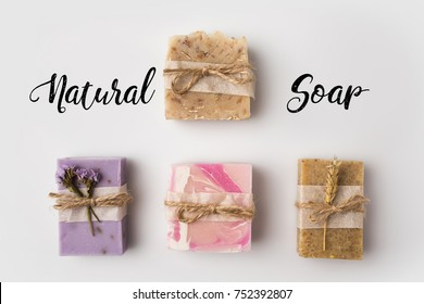 top view of different handcrafted soap with natural soap lettering on white surface