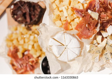 Top view of different kinds of cheese and meat on table ready for eating. Snacks for cocktail party. Horizontal color photography.