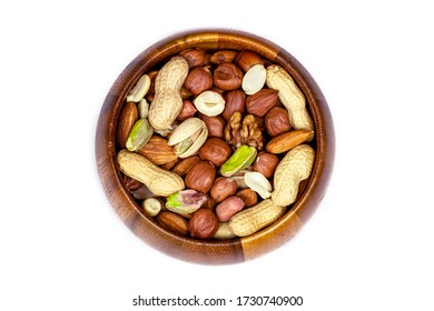 Top view of different nuts mix: almonds, pistachios, peanuts, hazelnuts heap in round brown wooden bowl isolated on white background
