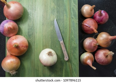 top view of a different size of a organic onions from a farmers market on a green cutting board with one onion without skin and dried roots and kitchen knife on side on a black kitchen granite top