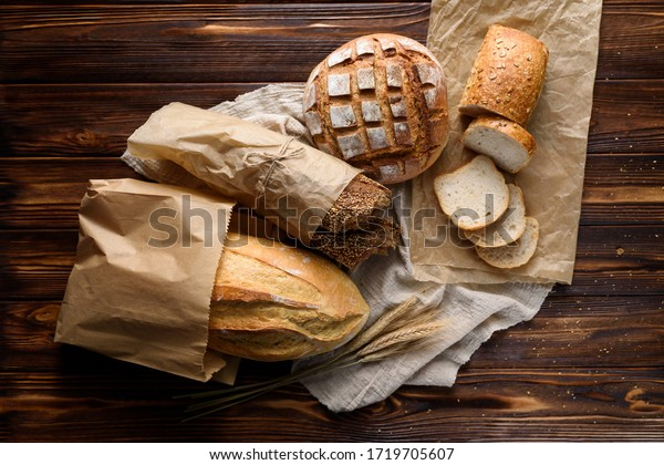 Top view of different types of tasty freshly baked bread in paper bags on a wooden rustic table.