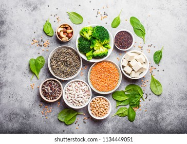 Top view of different vegan protein sources: beans, lentils, quinoa, tofu, vegetables, spinach, nuts, chickpeas, rice, stone rustic background. Healthy balanced vegetarian nutrition for vegans