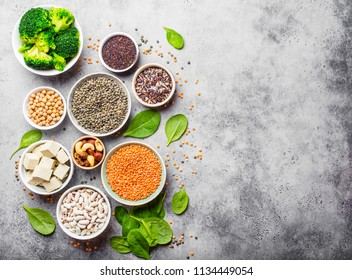 Top view of different vegan protein sources with space for text: beans, lentils, quinoa, tofu, vegetables, nuts, chickpeas, rice, stone background. Healthy balanced vegetarian nutrition for vegans