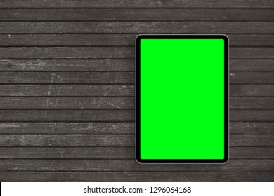 Top view of digital tablet computer with green isolated screen on wooden desk. Concept workplace.