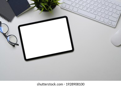 Top view of digital tablet with empty screen, glasses, plant and keyboard on white office desk.