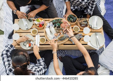Top view of dining table with seafood and seafood sauce. Men and women eating lunch together.
