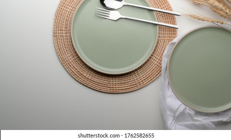 Top view of dinning table with mock-up turquoise ceramic plates and silverware on placemat and napkin on white table