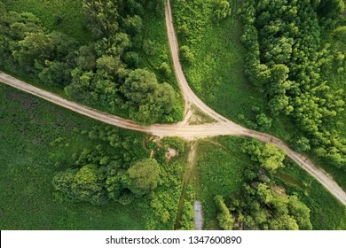 Top view of the dirt road with a crossroads and dense green forests. Beautiful bright landscape photography with drone on a summer day