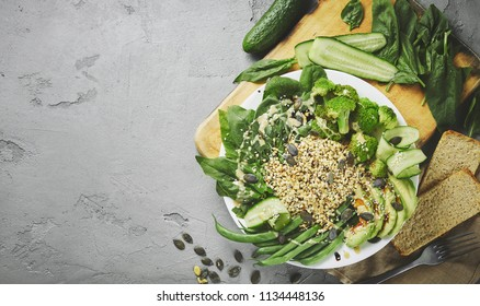 Top view of a dish with salad from raw buckwheat sprouts, broccoli, sticks of asparagus beans, cucumber, avocado, spinach and seeds. vegan food concept