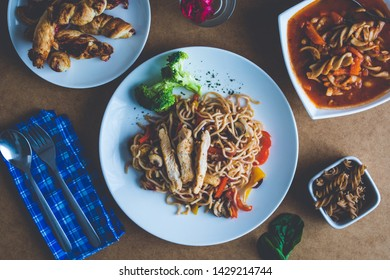 Top view dishes of Asian noodles, minestrone and jam pastry