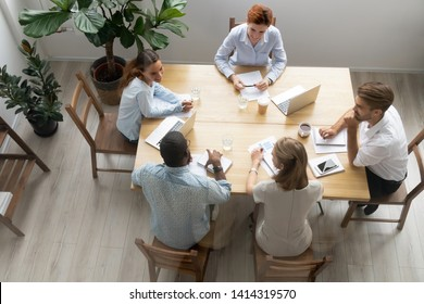Top view diverse businesspeople at meeting, briefing, during seminar, training courses. Coworkers informal chatting, partners discussion startup project results contract detail, reviewing sales stats