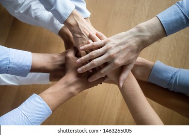 Top view of diverse businesspeople stack join hands showing unity and team spirit, promise support at work, loyal colleagues engaged in teambuilding motivated for shared success. Teamwork concept