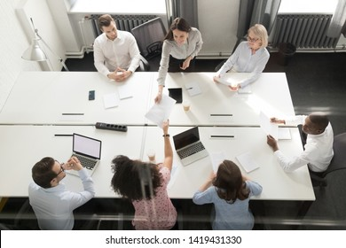 Top view of diverse employees sit at shared office desk hand paperwork material handout at meeting, multiethnic workers brainstorm check analyze paper statistics documents at company briefing