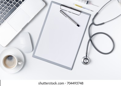 Top view of doctor desk table with stethoscope, coffee  and blank paper on clipboard with pen. Top view with copy space, flat lay.