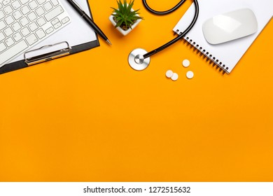 Top view of doctor's desk with stethoscope keyboard notepad and pen, prescription and pills with space for your text.