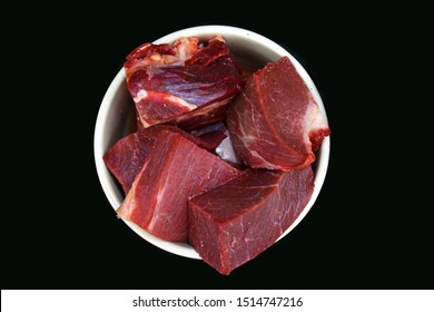 Top view of dog bowl with big red chunks of meat used for dog or cat raw biologically appropriate feeding on dark black background